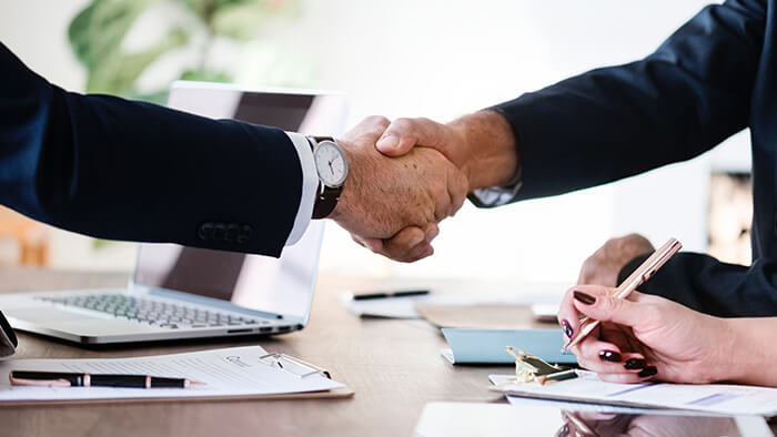 Two Business Men Shaking Hands Over Desk